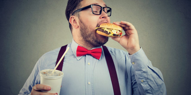 Overweight business man eating with appetite a burger holding a can of soda drink