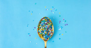 Microplastic in a spoon on blue background. microplastic in water and food. Microplastic problem. Dangerous additives. Toxic substances.
