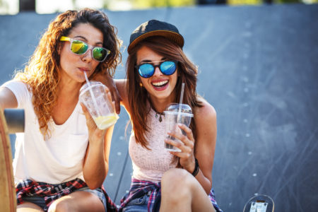 Two female friends hangout at the city street.Laughing and fun.Drinking juice.Two female friends hangout at the city street.Laughing and fun.Drinking juice.