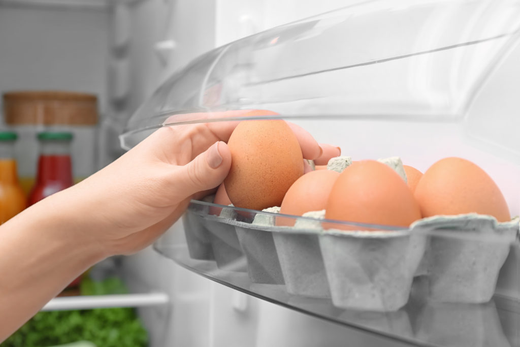 Woman taking chicken egg from refrigerator door shelf, closeup