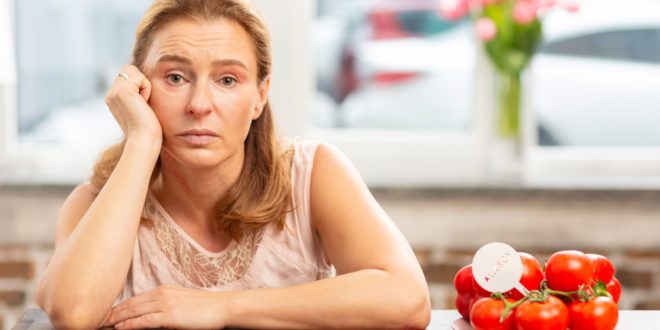 Mature blond-haired woman sitting at the table having food allergy