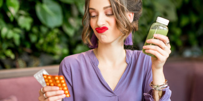 Woman with pills and healthy food