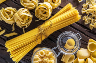 Different pasta types on the wooden table.