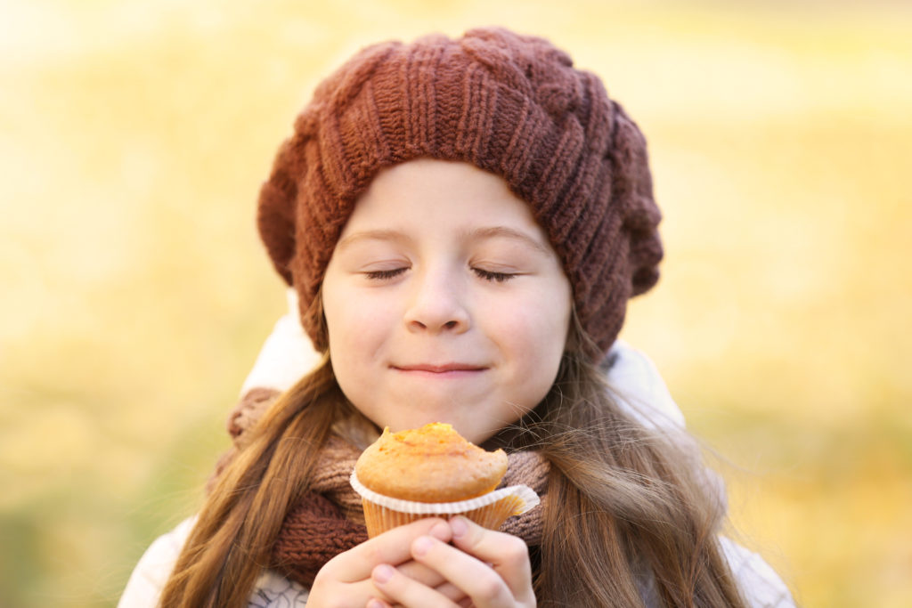 Cute little girl eating tasty muffin outdoors, close up view merendine