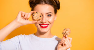 Close up photo of charming lovely hipster playing with cakes pies candies in kitchen preparing for birthday dressed in white woolen pullover isolated over colorful background