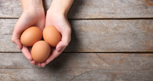 Woman holding raw eggs on wooden background