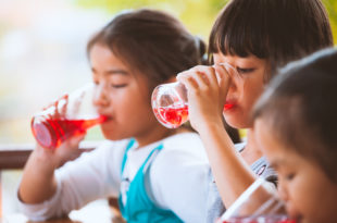 roup of asian children drinking red juice water with ice from glass together in the summer time