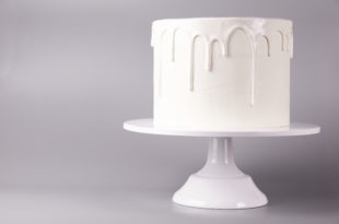 Simple white cake with glaze on a gray background.