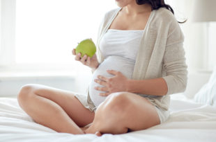 close up of pregnant woman eating apple at home