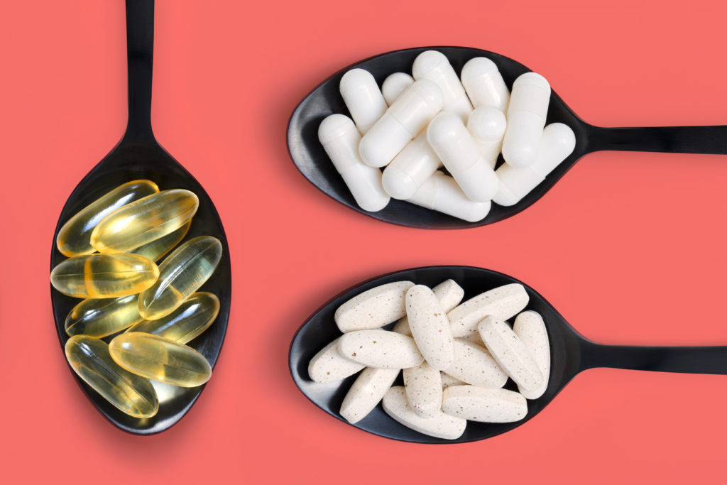 Healthy vitamin supplements on black spoons against pink color background