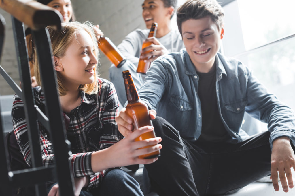 smiling teenagers sitting on stairs, drinking beer and talking