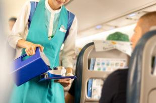 Flight attendant serving drinks to passengers on board.
