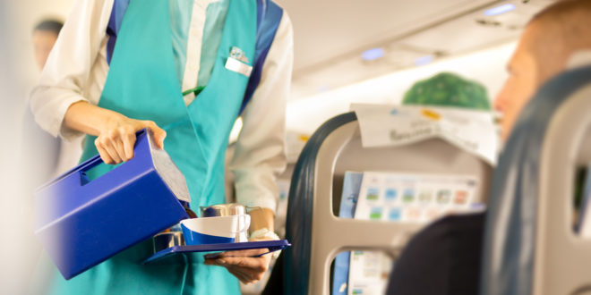 Flight attendant serving drinks to passengers on board.