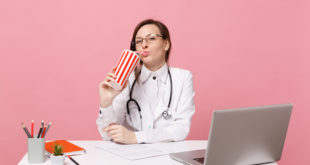 Female doctor sit at desk work on computer with medical document hold cola in hospital isolated on pastel pink wall background. Woman in medical gown glasses stethoscope. Healthcare medicine concept.