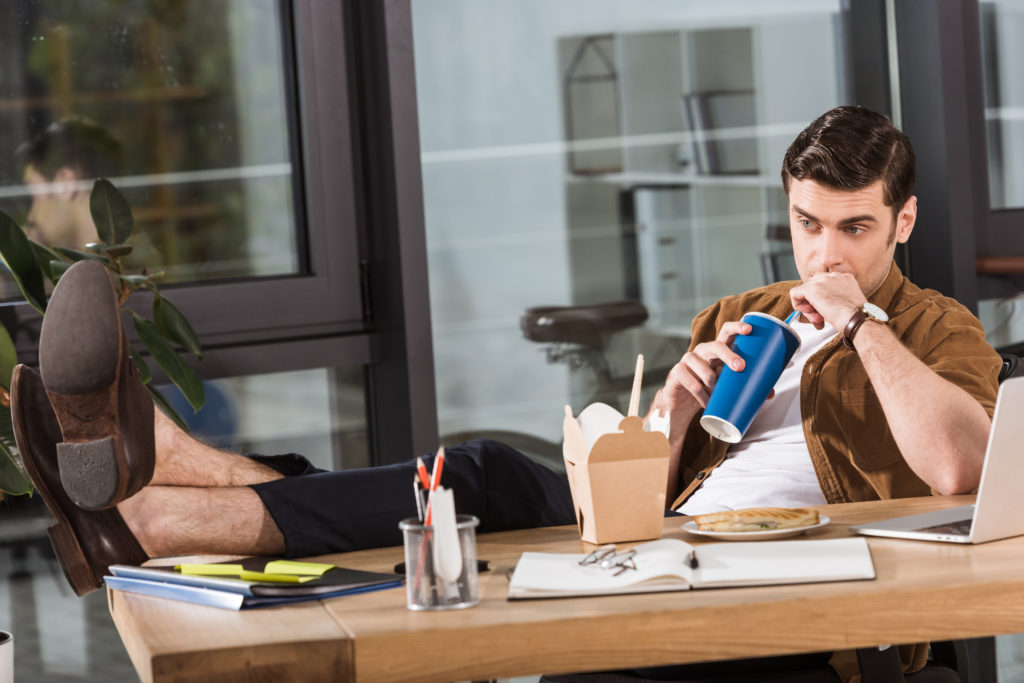 attractive businessman having lunch and drinking soda at workplace in office