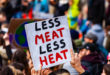 Homemade poster at ecological protest. A close-up shot of a homemade poster, saying less meat less heat, being held above a crowded street of environmental demonstrators.