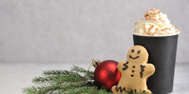 Cappuccino and cinnamon in a paper cup. Coffee is complemented by a gingerbread man and Christmas tree decoration.