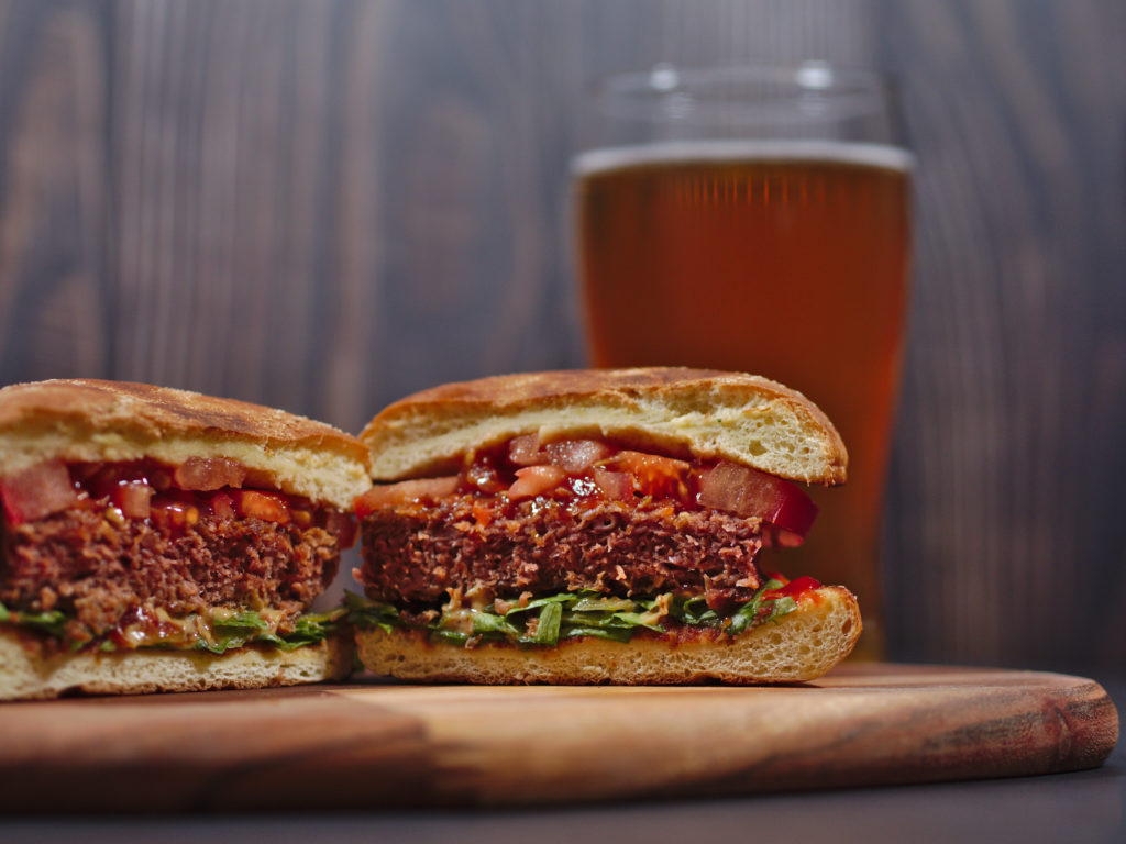 vegan plant based burger served on rustic cutting board with beer