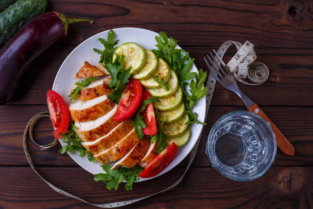 Diet concept, healthy lifestyle, low calorie food. Baked chicken breasts with zucchini and salad, measuring tape, glass of water and vegetables on the table