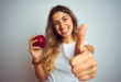 Young beautiful woman eating red apple over grey isolated background happy with big smile doing ok sign, thumb up with fingers, excellent sign