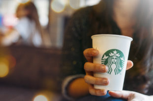 New York, USA - November 5, 2019 : Close up of a Woman drinking a tall Starbucks coffee in starbucks coffee shop with carrot cake. ManuPadilla - stock.adobe.com