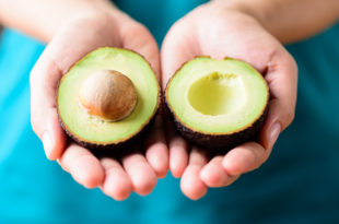 Half avocado fruit holding by hand, healthy fruit