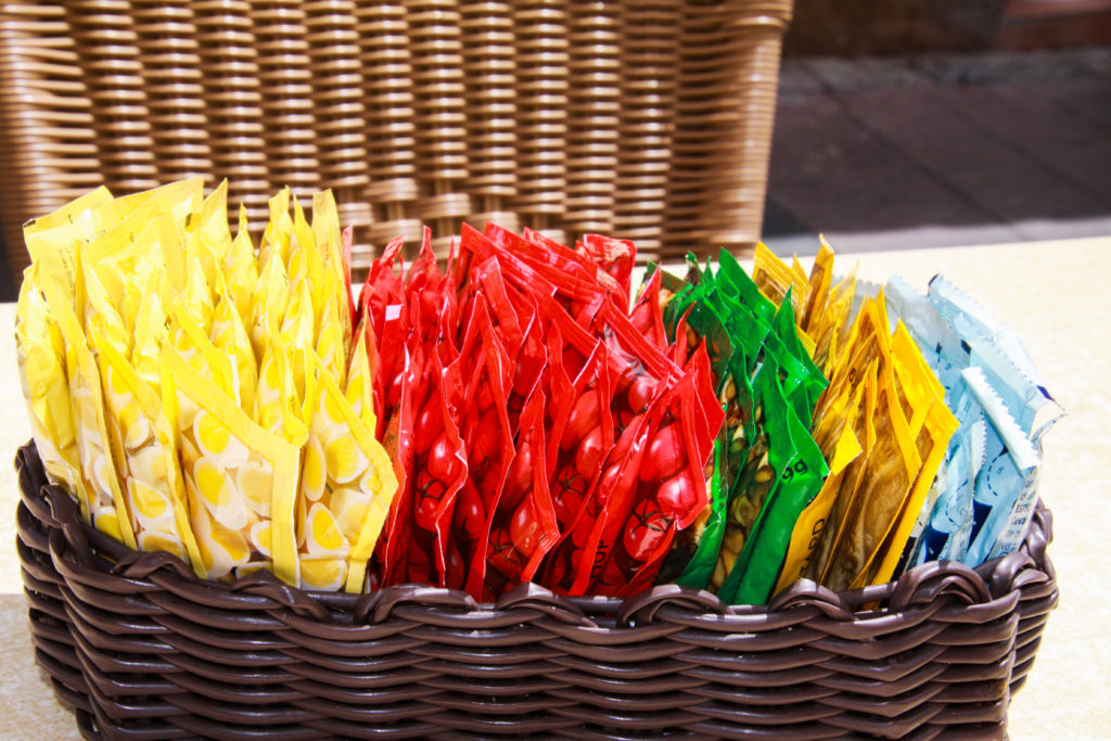 Close up of wooden basket with choice of small colorful plastic packages of sauces on table of restaurant outdoor
