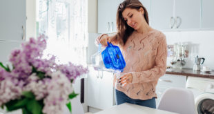 Woman pouring filtered water from filter jug into glass on kitchen. Modern kitchen design. Healthy lifestyle
