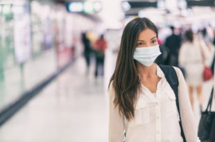 Coronavirus Asian woman walking with surgical mask face protection walking in crowds at airport train station work commute to hospital.