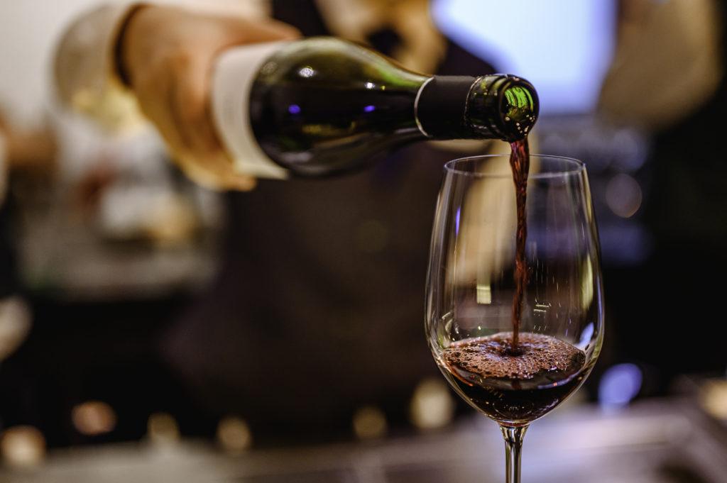 Derramando um copo de vinho tinto de uma garrafa.