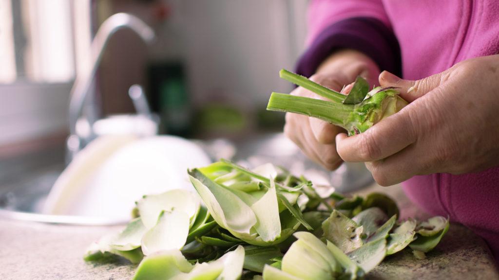 Cleaning artichoke with knife. Peeling off artichokes