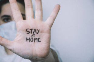"Woman on a side with his hand facing in front with the sentence ""stay at home"" written on the palm of her hand. Coronavirus concept."