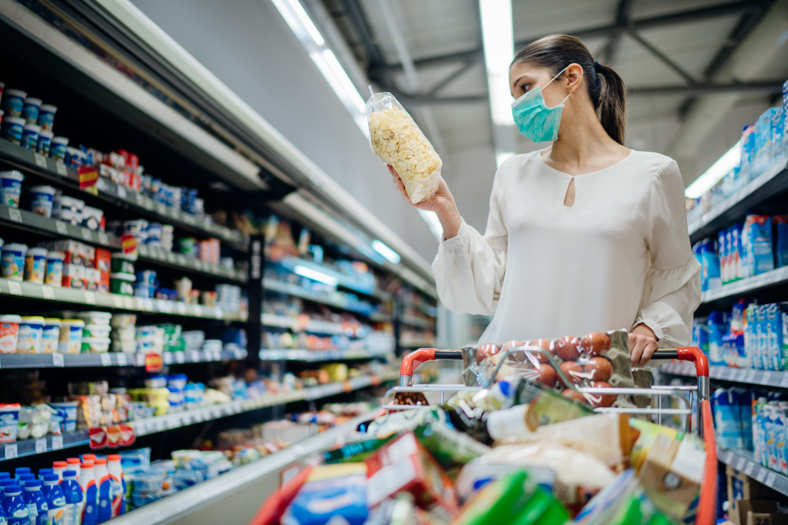 packaging, Young person with protective face mask buying groceries/supplies in the supermarket.Preparation for a pandemic quarantine due to coronavirus covid-19 outbreak.Choosing nonperishable food essentials