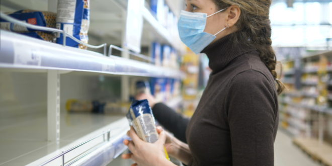 A woman in a medical mask takes the last bag of cereals in the store, empty supermarket shelves.