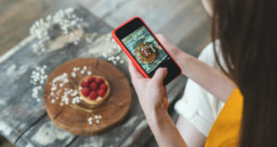 Young adult food stylist woman taking photo on smartphone