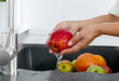 Cook woman washes an apple under running water from a water tap.