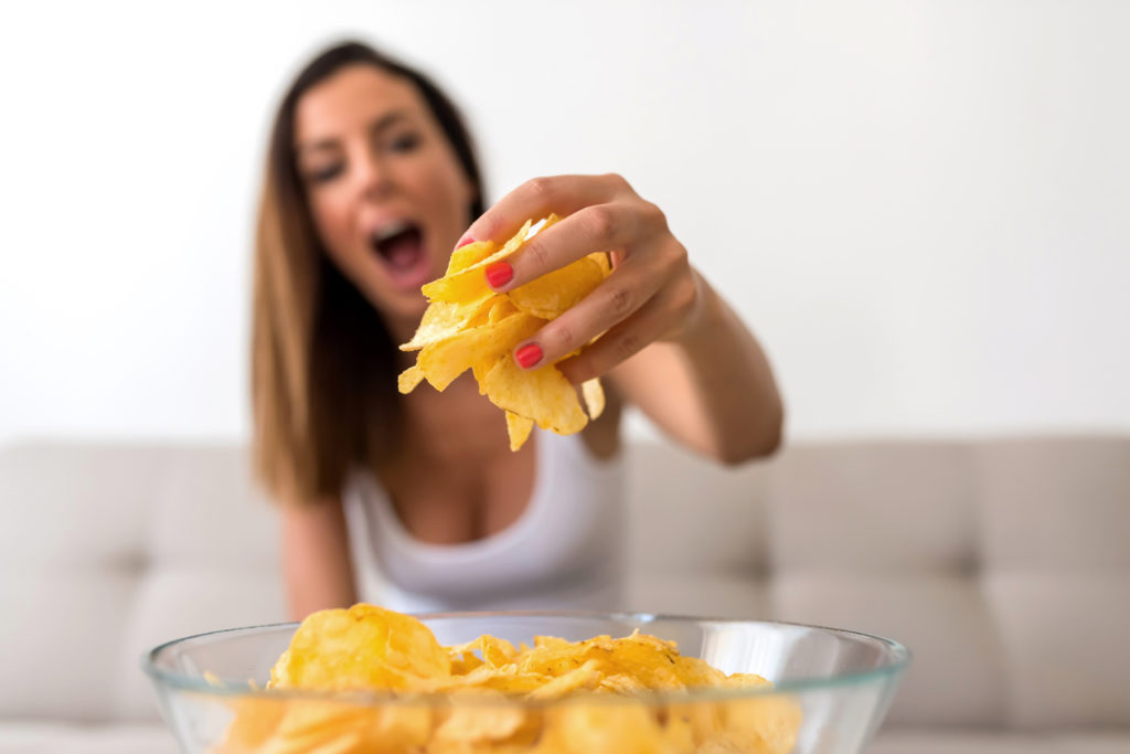 A young beautiful Woman relaxing on a sofa having potato Chips