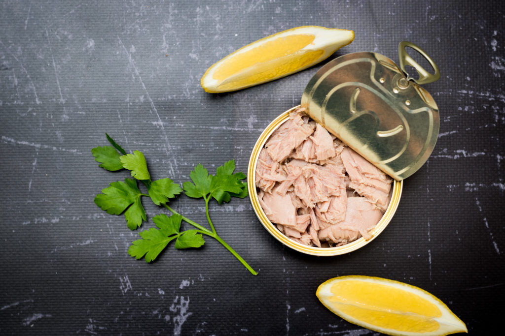 Canned tuna with lemon and parsley on dark background, top view.