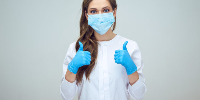 woman doctor wearing medical mask doing thumb up.