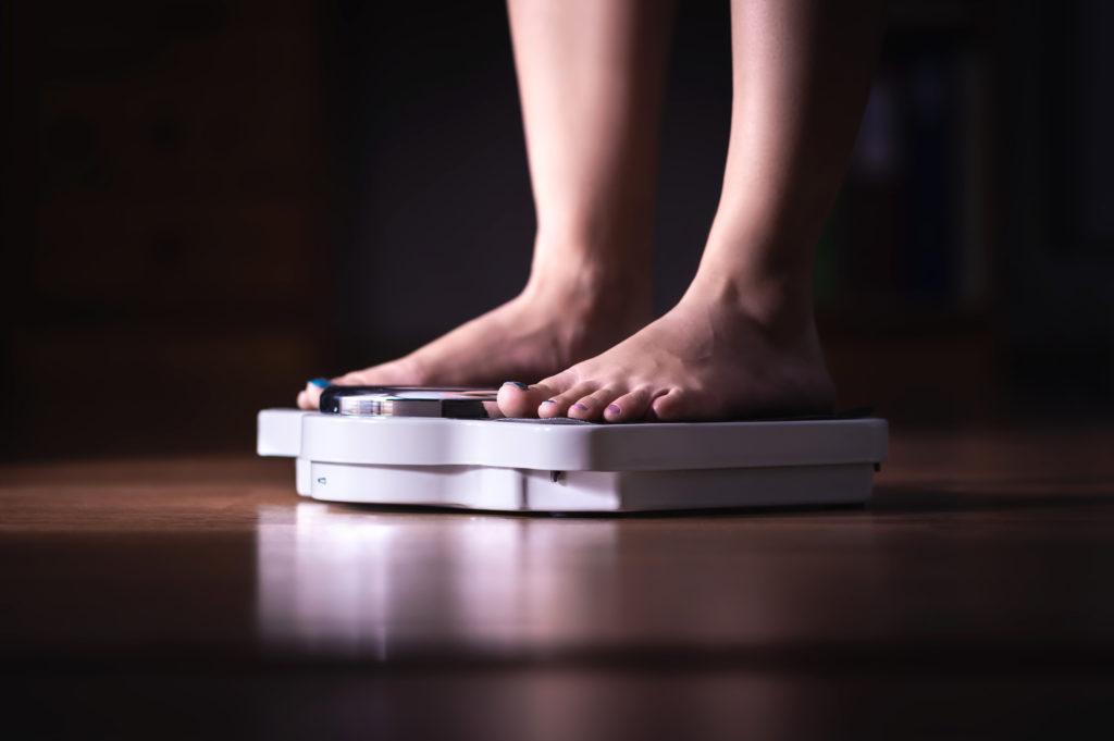 Pés em escala. Conceito de perda e dieta de peso. Mulher se pesando. Senhora de aptidão fazendo dieta. Perda de peso e dietética. Humor escuro da noite.