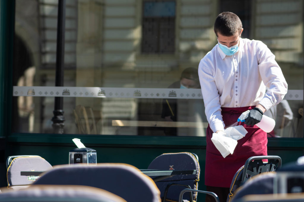 Waiter with a mask disinfects the table of an outdoor bar, café or restaurant, reopen after quarantine restrictions