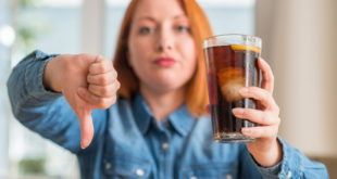 Redhead woman holding soda refreshment with angry face, negative sign showing dislike with thumbs down, rejection concept sugar tax