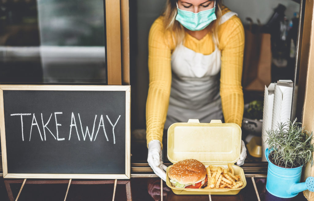 Young woman preparing takeaway food inside restaurant during Coronavirus quarantine time - Girl inside kitchen working while cooking delivery food for online take away service - Focus on hamburger