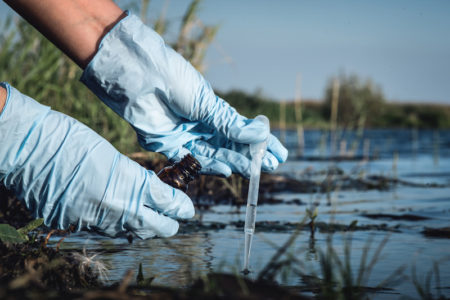 acqua fiumi analisi inquinamento ambiente Water pollution concept. Woman scientist takes a water sample from polluted pond.