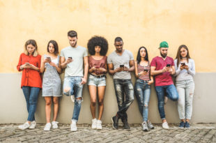 Multiracial friends using smartphone against wall at university college backyard - Young people addicted by mobile smart phone - Technology concept with always connected millennials - Filter image