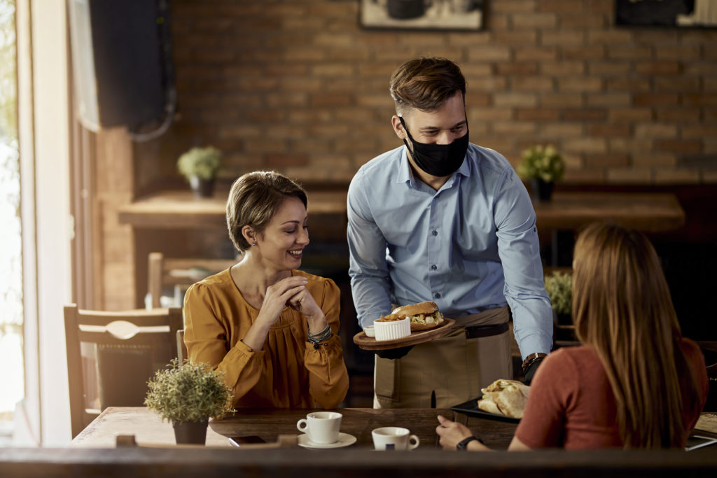 Happy waiter wearing protective face mask while serving food to guests in a restaurant.