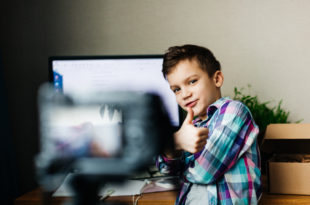 child blogger shoots video on camera, smiling, unpacking blog, video recording at home for blog for followers