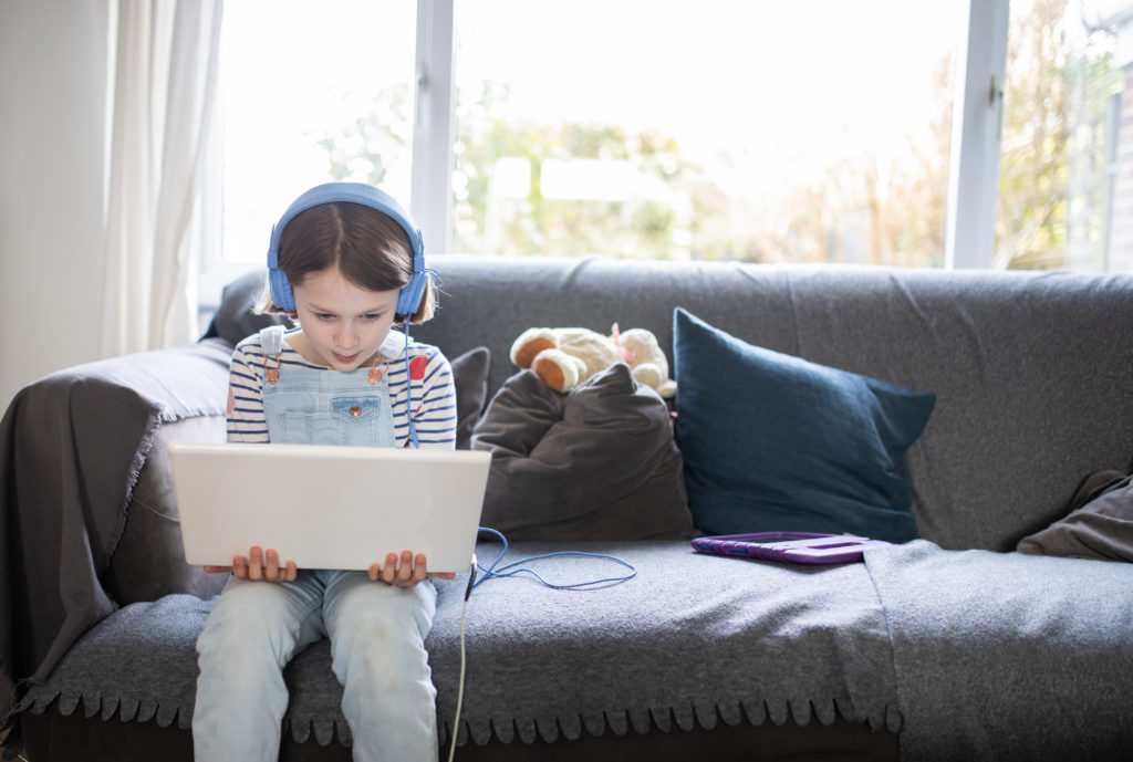 female child sitting on the sofa at home with a laptop and head phones