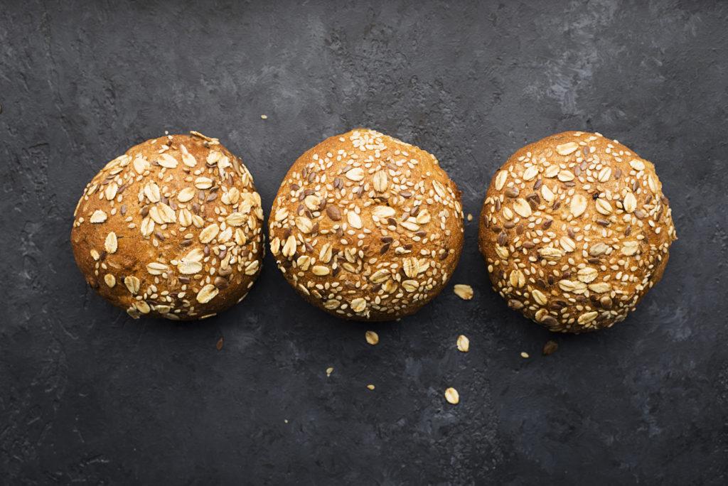 Wholegrain burger buns on dark background. Top view, space.