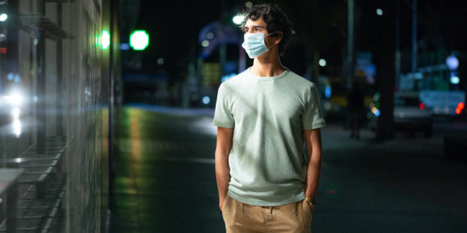 Handsome young man with face mask walks looking at empty shelves in a shop on city street at night
